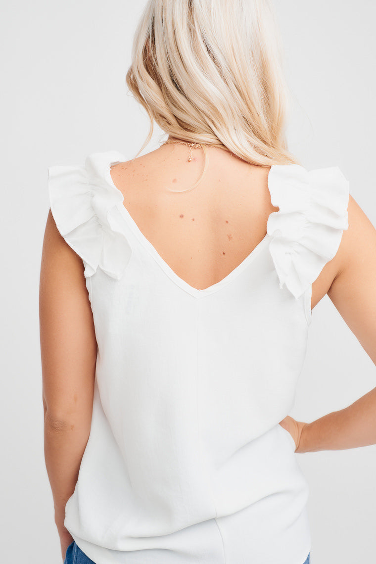 This lightweight white tank has ruffled flutter sleeves attach on a v-neckline that flows into a relaxed bodice. Pair this with a pencil skirt and pumps.