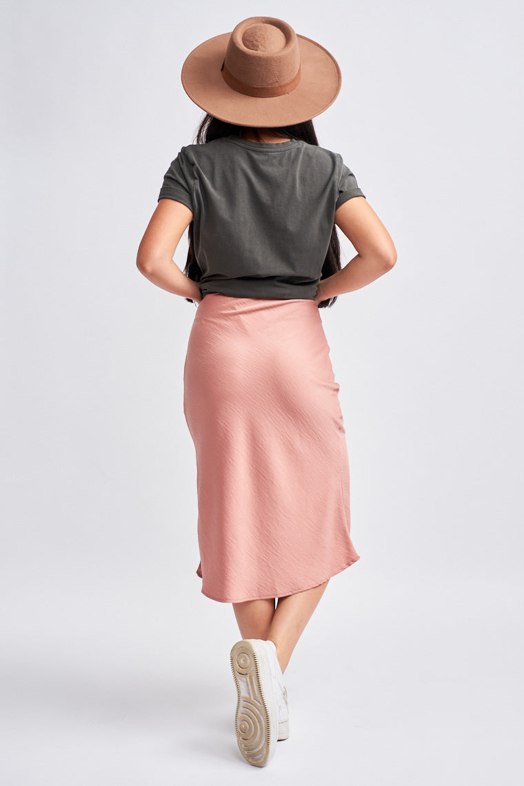 This satiny skirt has an elastic waistband that leads into a fitted then flowy skirt silhouette that meets mid-calf.