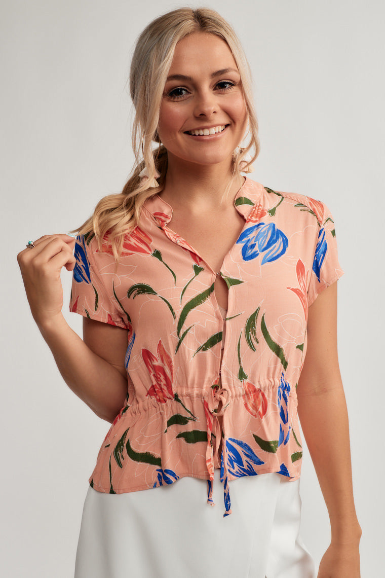 Beautiful pink sets the stage for colorful spring tulip flowers on a lightweight crop top with a multi-hoop and eye closure down the relaxed bodice, a drawstring waistline and capped sleeves.