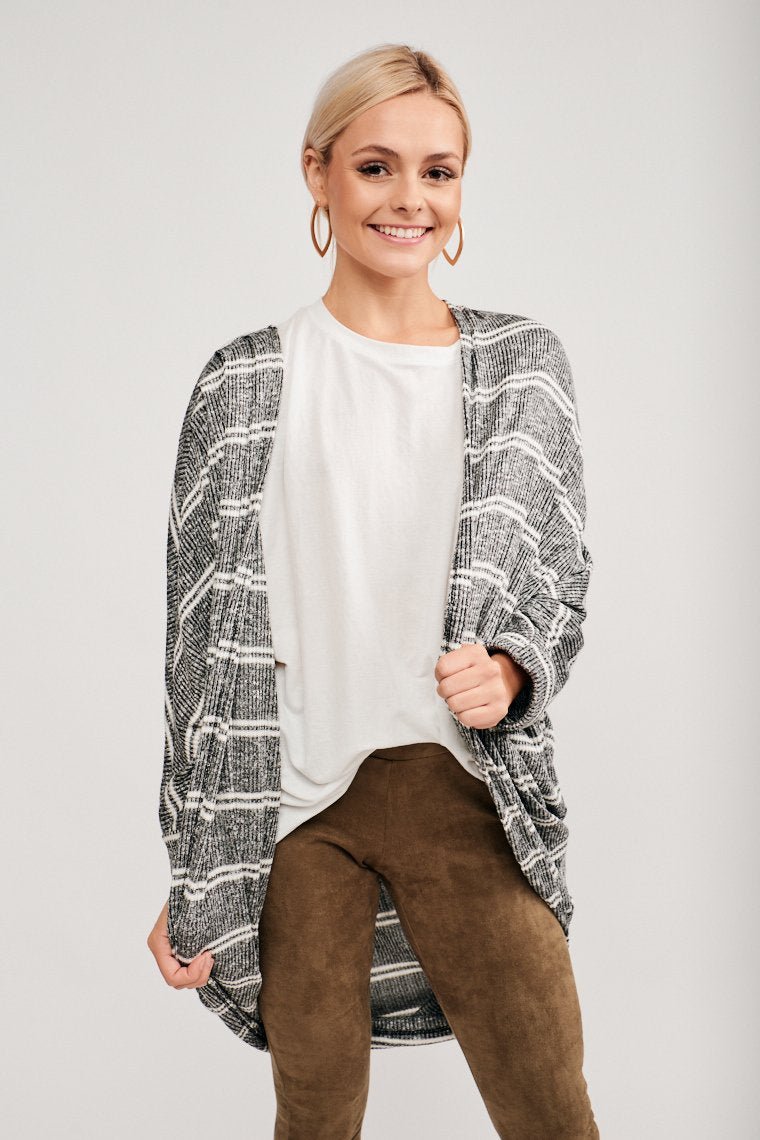 This striped knit cardigan has long cuffed sleeves that attach to an open-front silhouette, an oversized, slouched fit, and a long hemline.