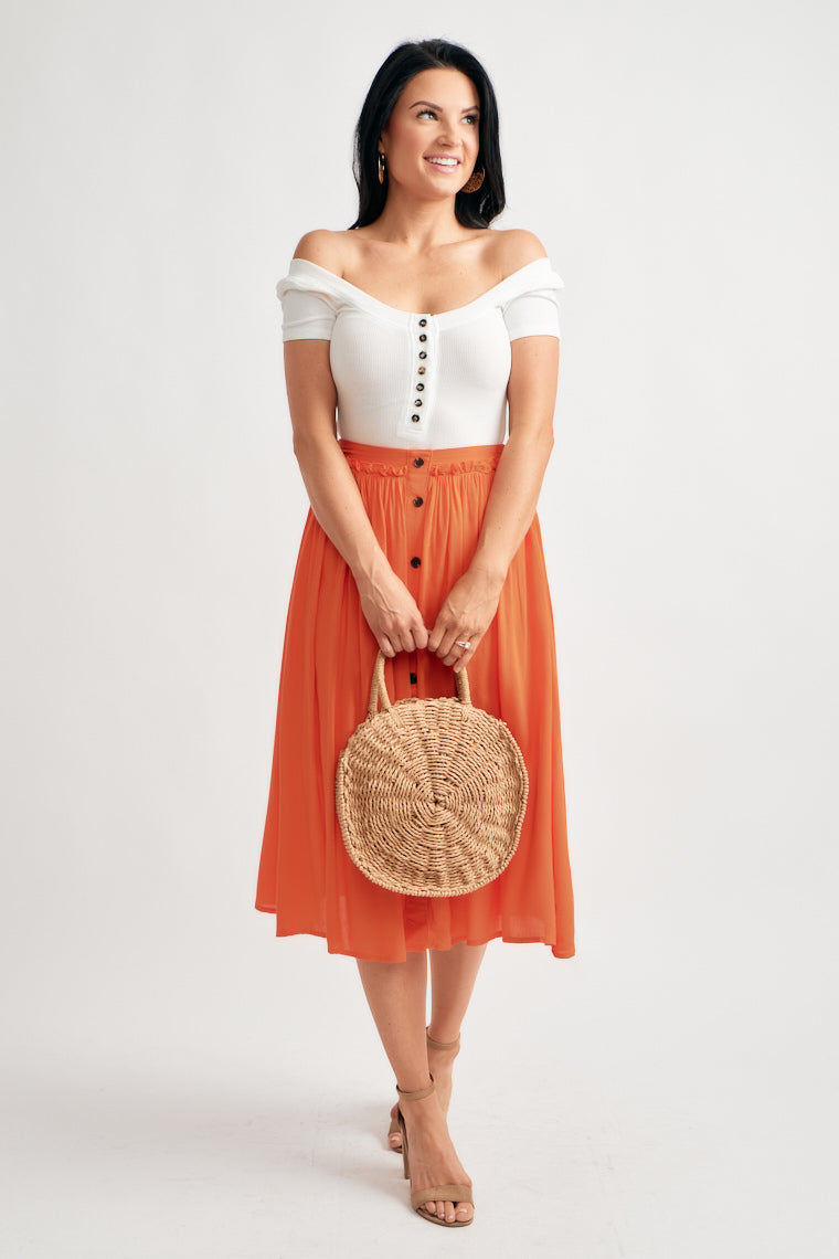 This vibrant maxi skirt offers a fitted waistline with a flowy, circle silhouette with buttons down the center.