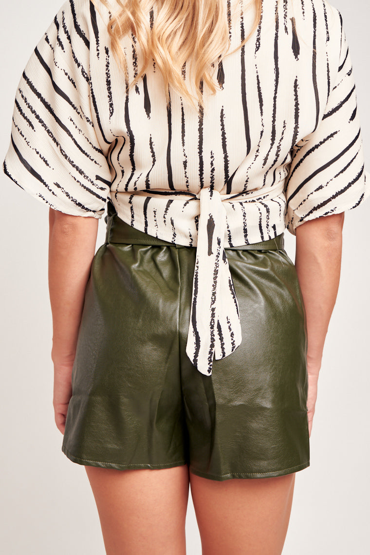 This skort has a paper bag top, belt loops and ties at the waist which leads to the skirt panel atop side pockets and relaxed shorts. Features a button and zipper closure.