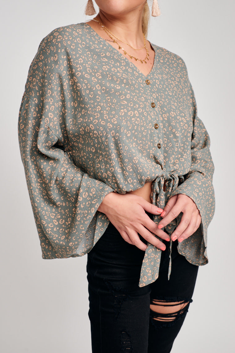 Taupe leopard print decorates this lightweight top with an elastic banded waist. Long sleeves attach to a v-neckline and lead to a relaxed button-down bodice and tie-front hem.