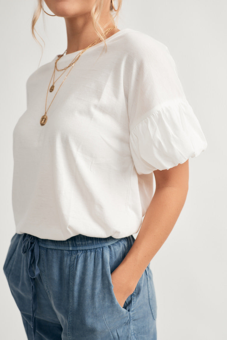 This basic white tee offers a crew neckline with a relaxed silhouette and some extra fun fluff on the short sleeves with ruffle detailing.