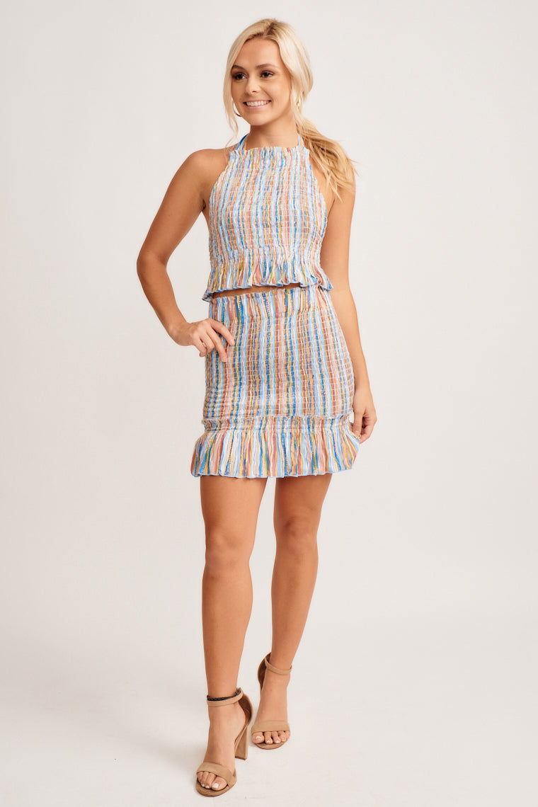 Shades of blue, brown, and green stripe this smocked skirt. This skirt has a ruffle hem at the bottom and hugs your body to accentuate your curves