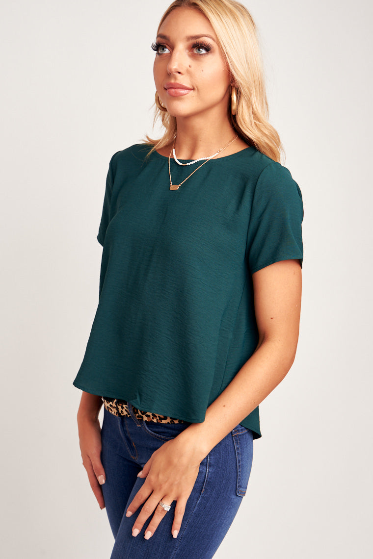 This top has short sleeves that attach onto a u-neckline and flow into comfortably relaxed and cropped bodice. This top has buttons detailing down the back.