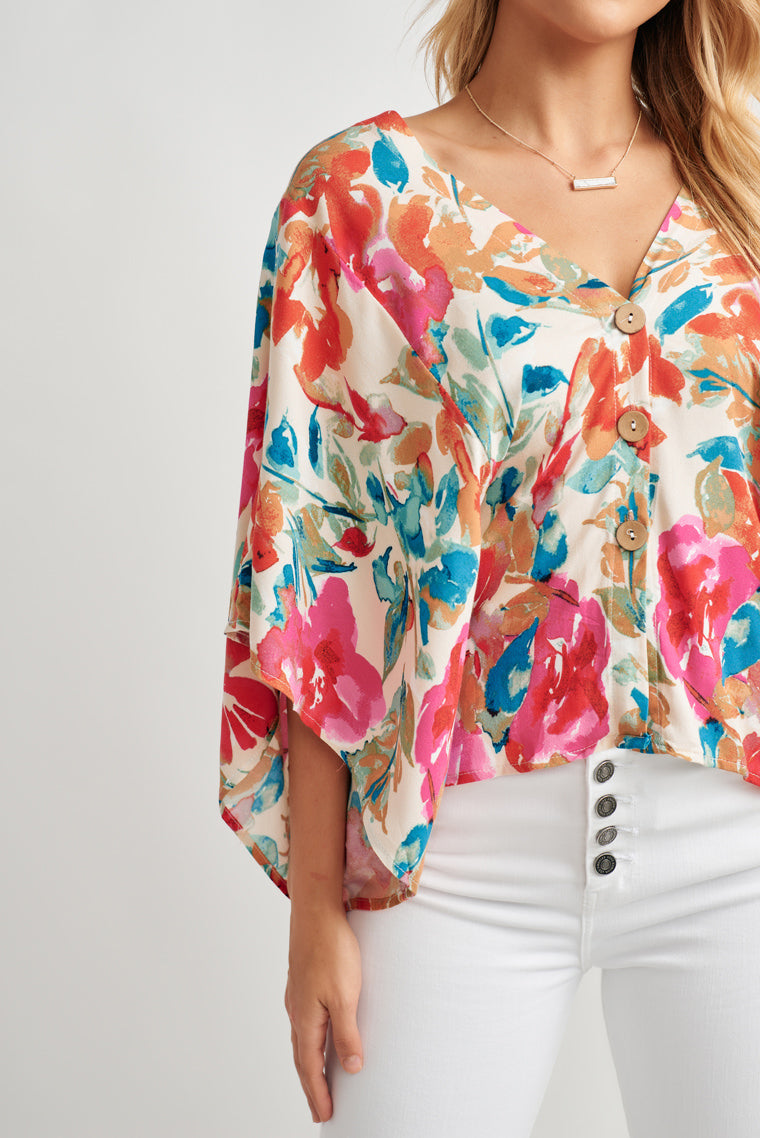 This gorgeous colorful floral print creates a v-neckline with an oversized, flowy, relaxed fit blouse with kimono sleeves and button-down center.
