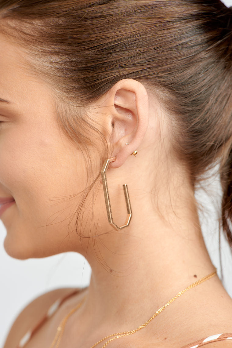 These earrings have a post that is attached to a long geometric drop hoop.