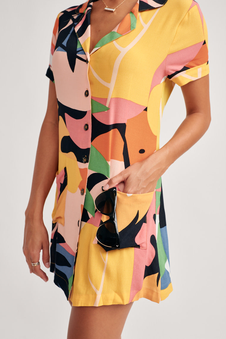 Tropical leaves in multiple colors lay overtop unique summer print that decorates this mini dress. The collared neckline carries into a button-down center.