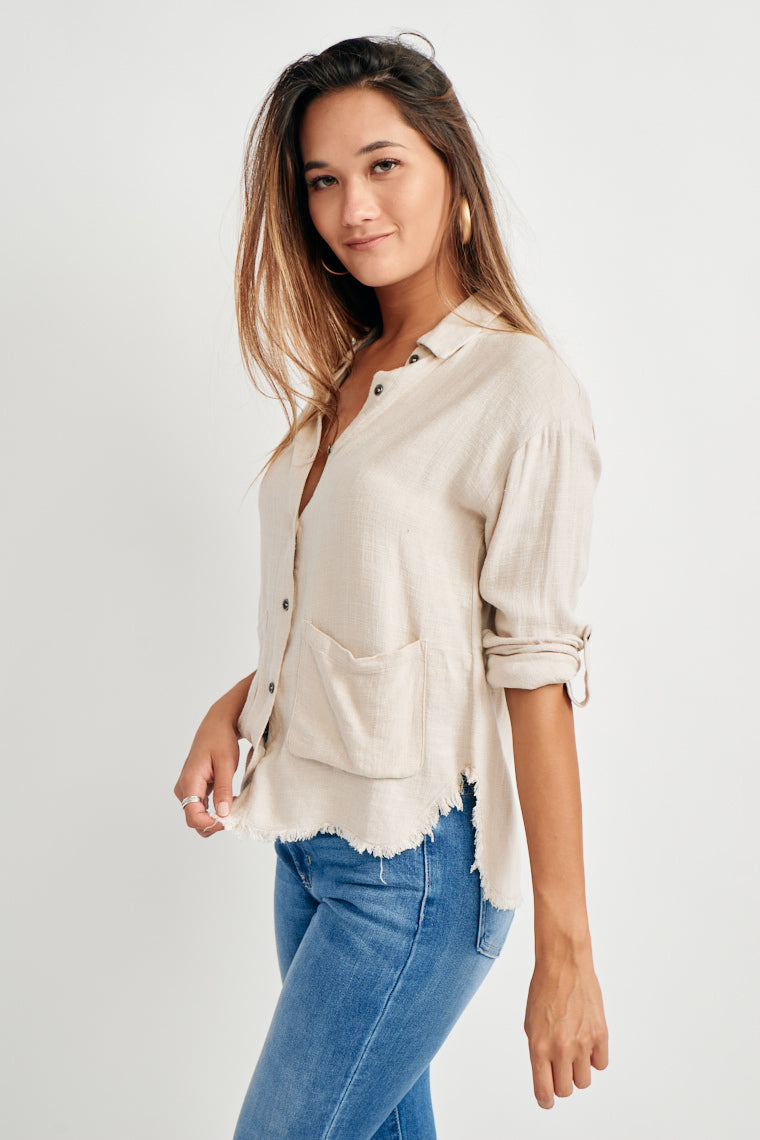 This lightweight blouse offers collared neckline transitions into a relaxed button-down silhouette with a raw edge hem and sleeves that roll up to button tabs.