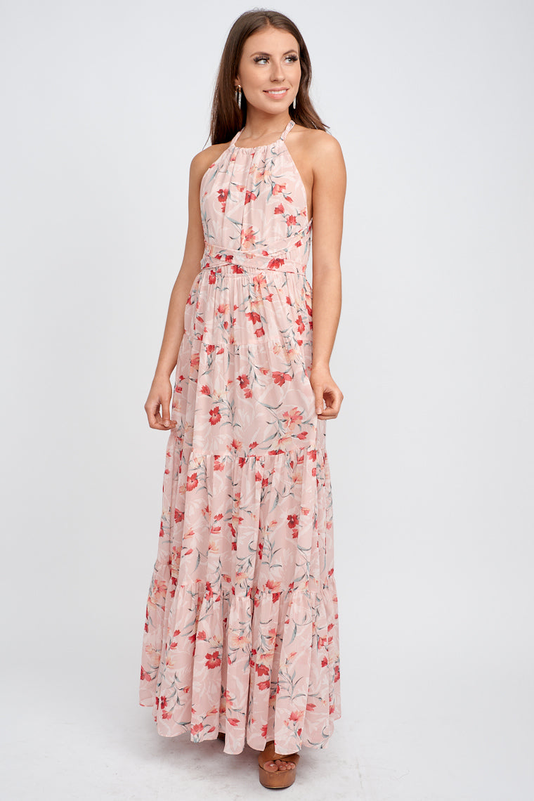 A high halter neckline that has a fabric tie that secures at the back, relaxed bodice which meets an elastic waistband and flows into a long tiered maxi skirt