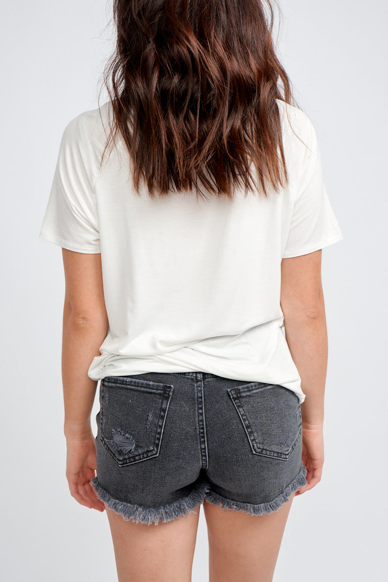 Black washed denim shorts have a traditional 5-pocket structure with a high button down waistband leading to distresses across the shorts and lead to a raw frayed hem.