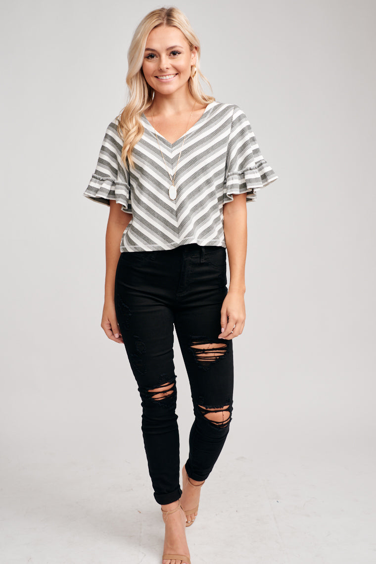 Shades of grey stripes go across this fun knit top, where medium sleeves with ruffle cuffs attach to comfortable knit and loosely fit cropped bodice.