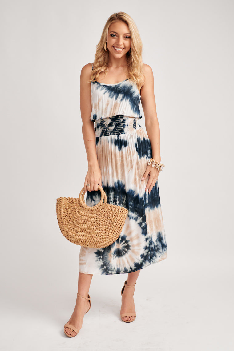 Shades of beige and blue tie-dye decorate this strap, scoop neckline that blouses over a smocked waistline and flows into a straight midi skirt with a side slit.