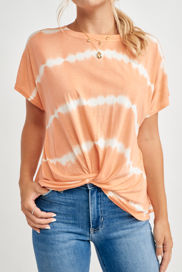 This super soft top offers a bright coral and white tie-dye print, rounded neckline with short sleeves and a relaxed fit with a twist front feature on the hem.