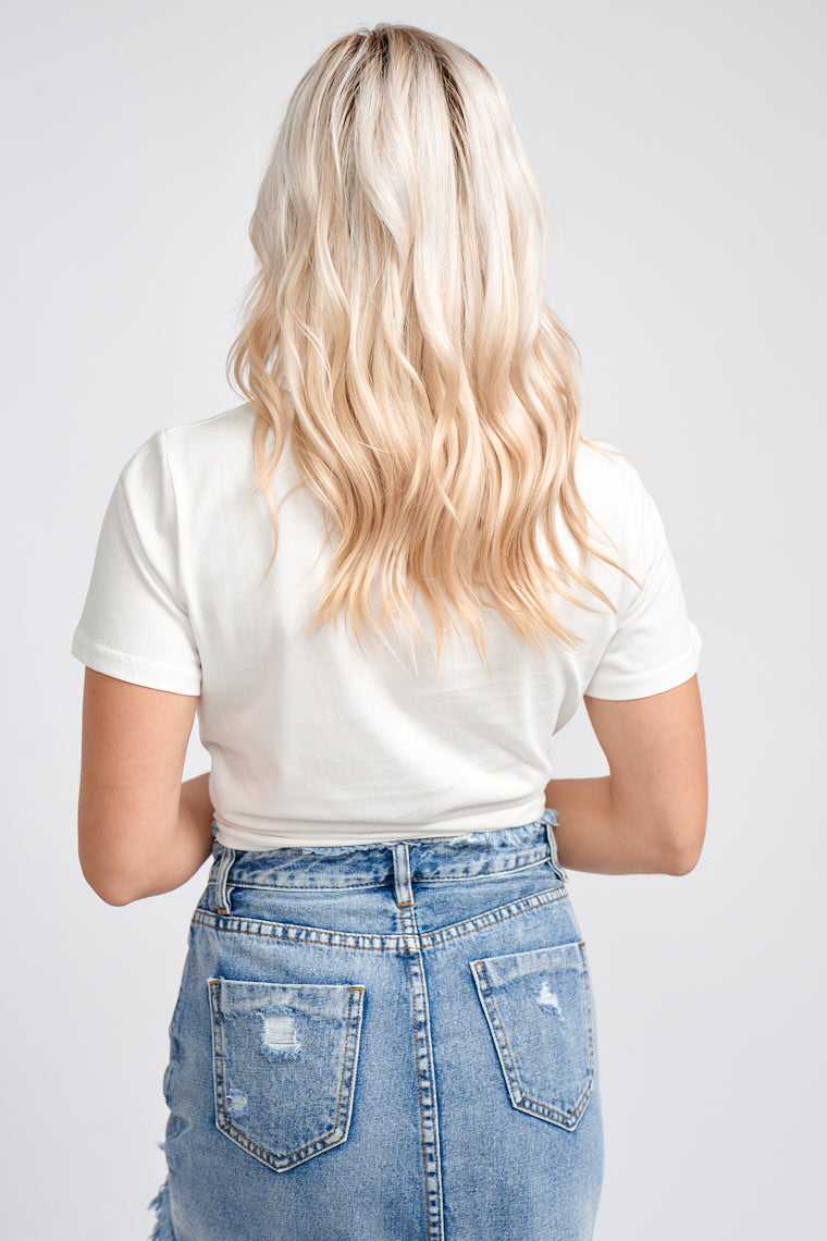 "Short sleeves that attach to a relaxed bodice with a cropped hem with a front pocket at the side. Imprinted on the front pocket, the words ""Omg Babe"" are in a black outlined text."