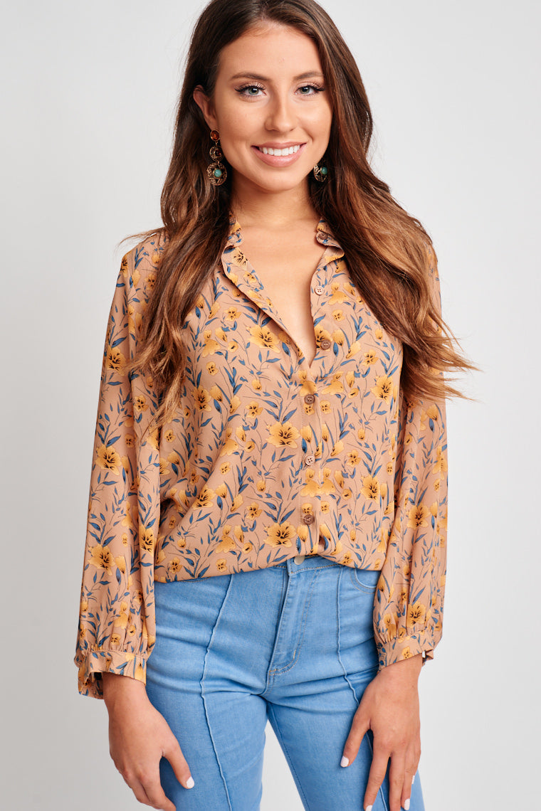 This collared printed blouse has loose long sleeves that are cuffed at the bottom and attach to a relaxed fit button-down bodice. Style by tucking into a pencil skirt.