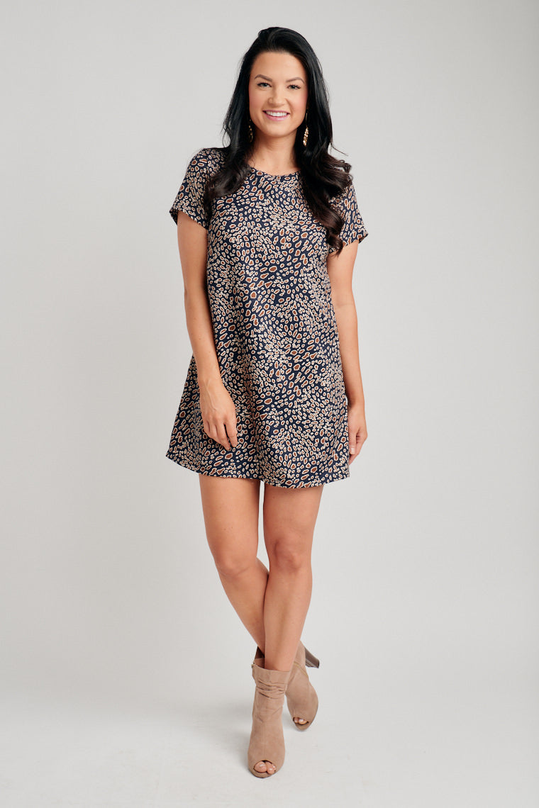 Brown spots speckle the fabric of this dress. Short sleeves that attach to a banded u-neckline and leads to a darted and relaxed shift dress silhouette.