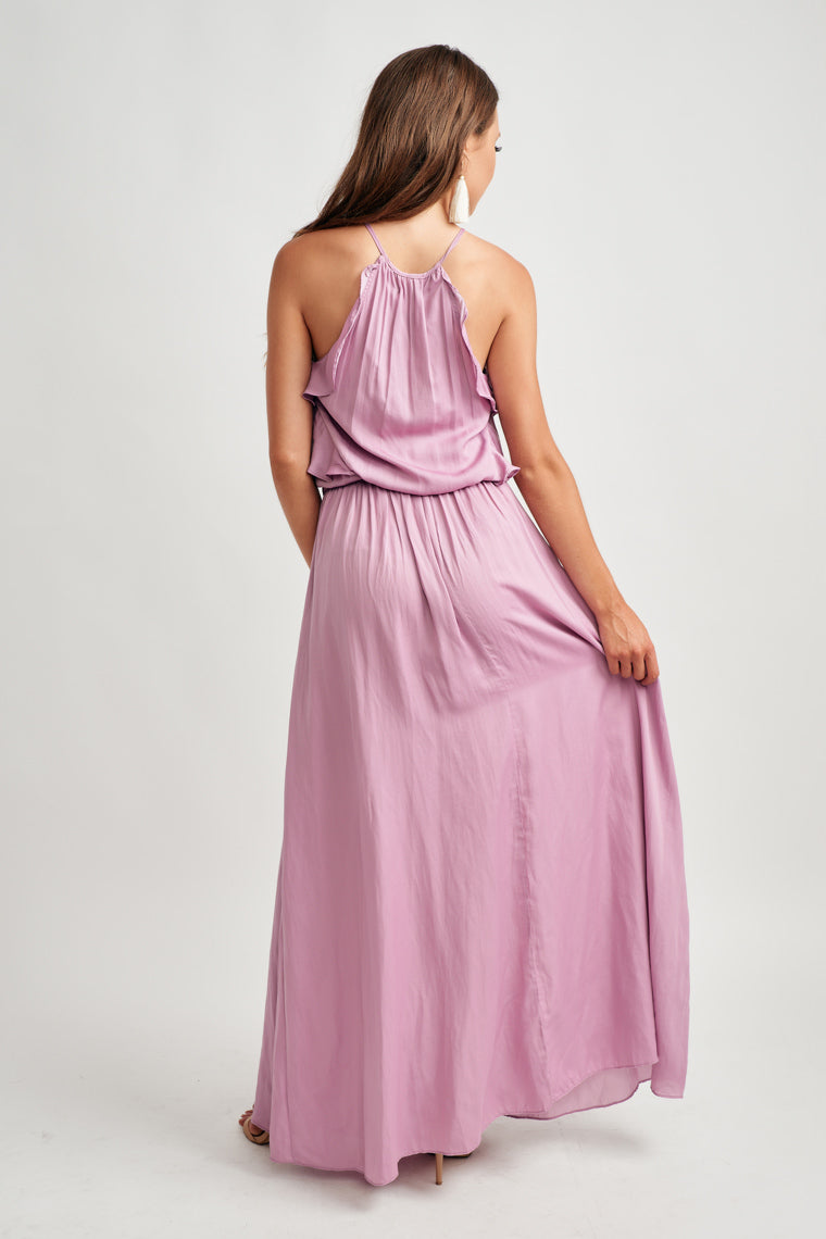 Starting at a high neck with a keyhole feature with cascading ruffle down the side bodice. The smocked waistline moves into a flowy and flirty maxi skirt.