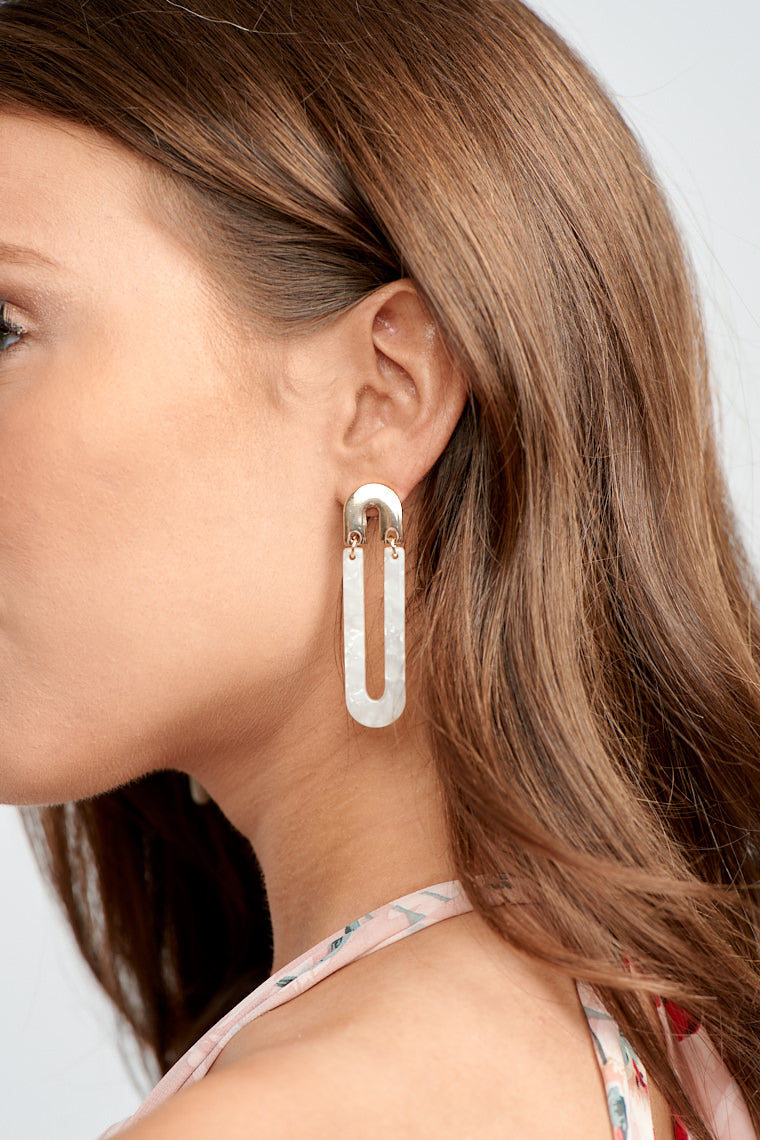 These lightweight earrings have a post that is attached to a small inverted u-shape and leads down to an extended white u-shaped drop.