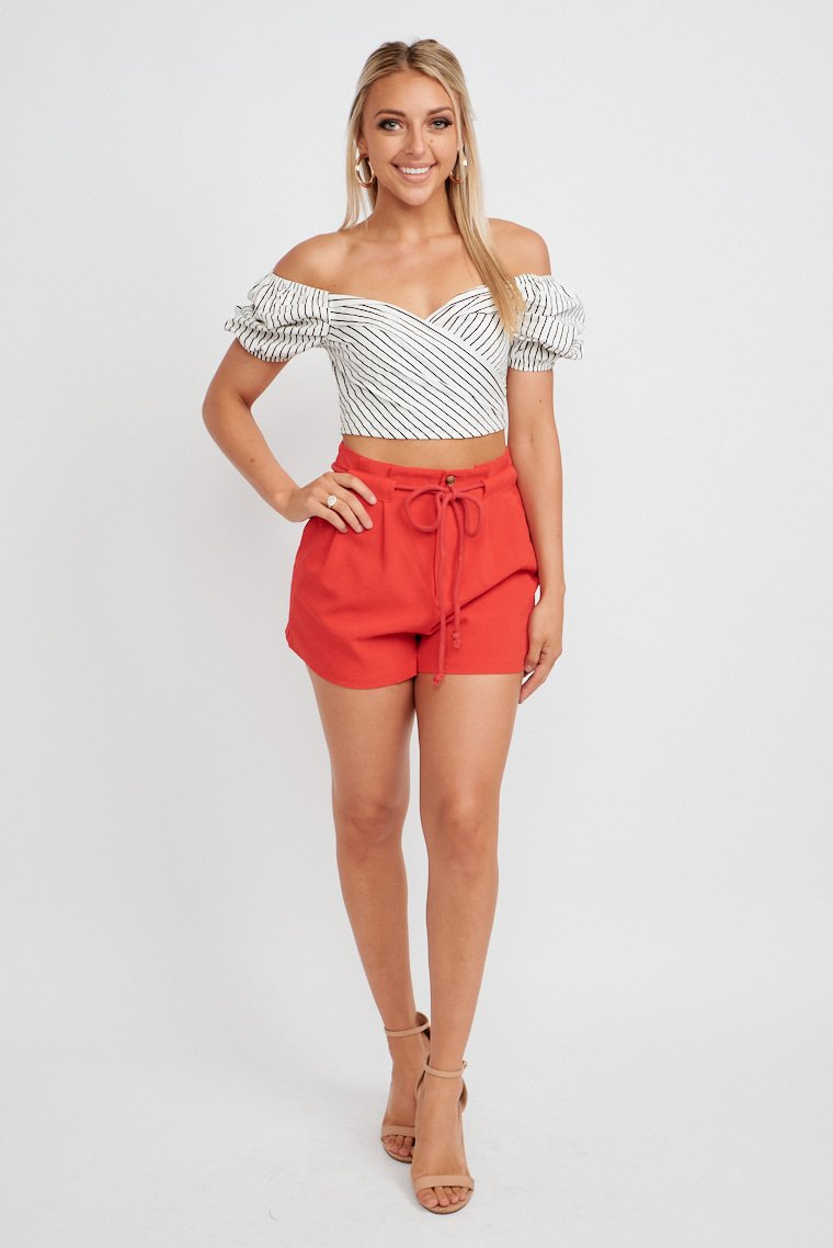 These bold red shorts have a modest paper-bag style waistband that leads to long belt loops with a and leads to relaxed shorts with pockets at the side.