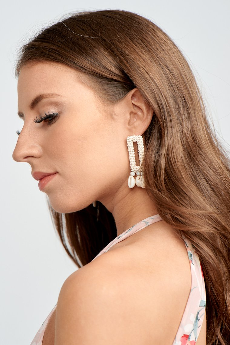 These earrings have a post with a square, micro-beaded drop body and lead down to beads attached to small shells at the bottom.