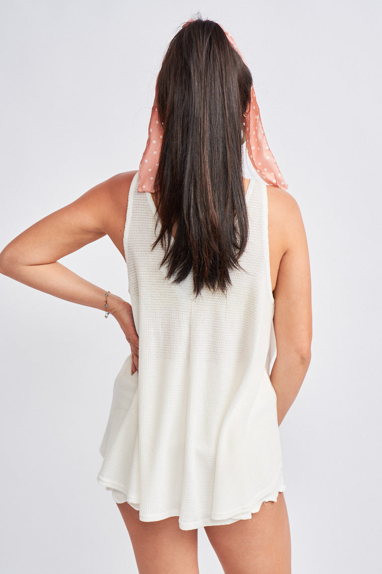 This tank top is lightweight and perfect for the warming weather. Medium straps attach to a deep v-neckline on a loose and oversized bodice silhouette with a high-low hem.