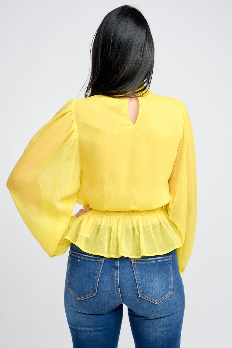 Long sheer button cuff sleeves attach to a high ruffled neckline on a relaxed bodice silhouette that leads to an elastic smocked waist that leads to a peplum-style hem.