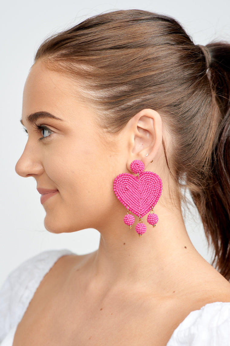 These earrings have a post that attaches to a circular beaded piece that leads to a large beaded heart with a darker tone bead trim and ends with three beaded spheres that dangle off of it.