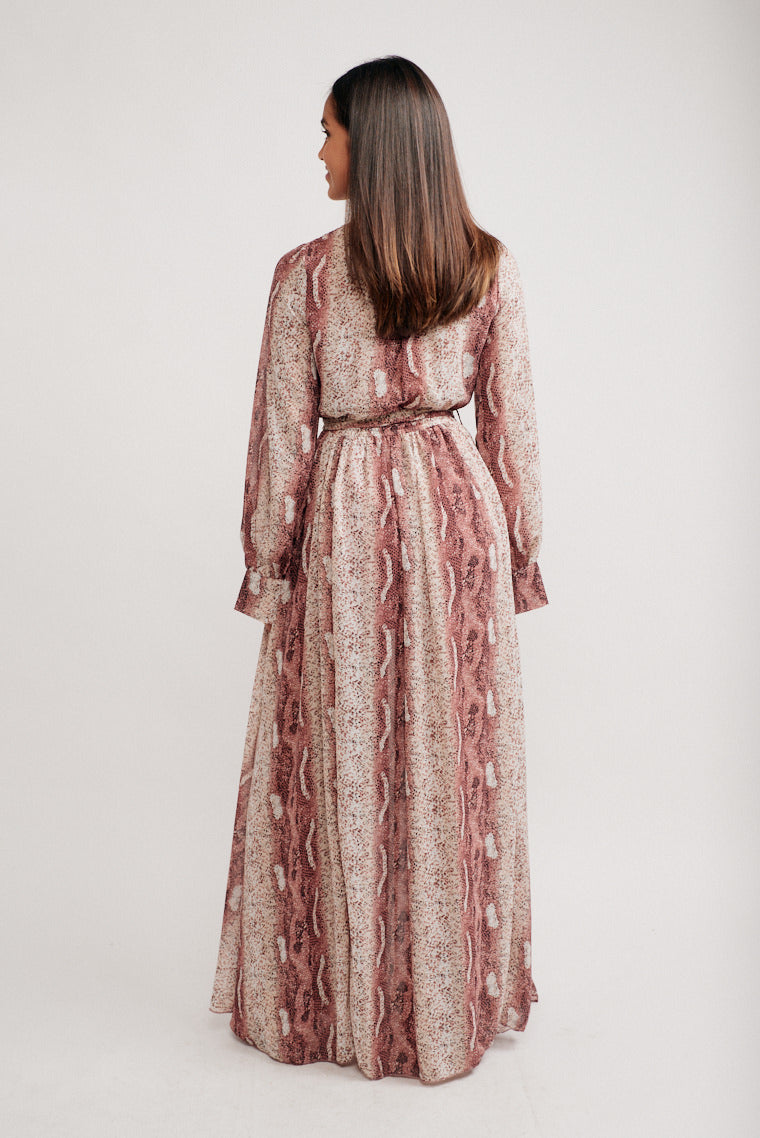 Long flowy sleeves that attach to a surplice neckline on a relaxed bodice silhouette and meets an elastic waistband and leads to a flowy skirt with a slit at the front.