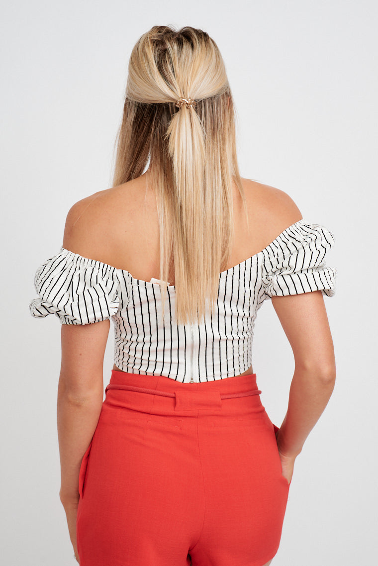 This darling striped top has short puffy sleeves that attach to an off-the-shoulder and surplice neckline into a fitted and cropped bodice silhouette.