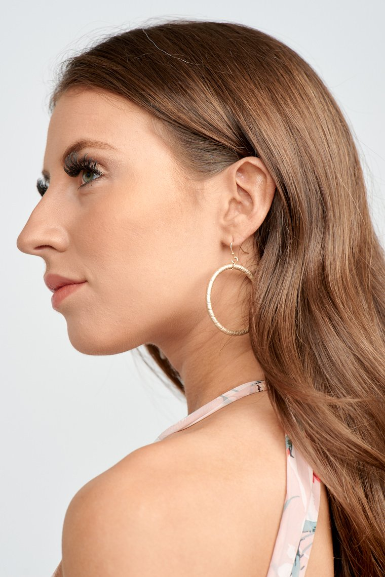 These earrings have a curved post that attaches to a circle drop shape that has winding details throughout.