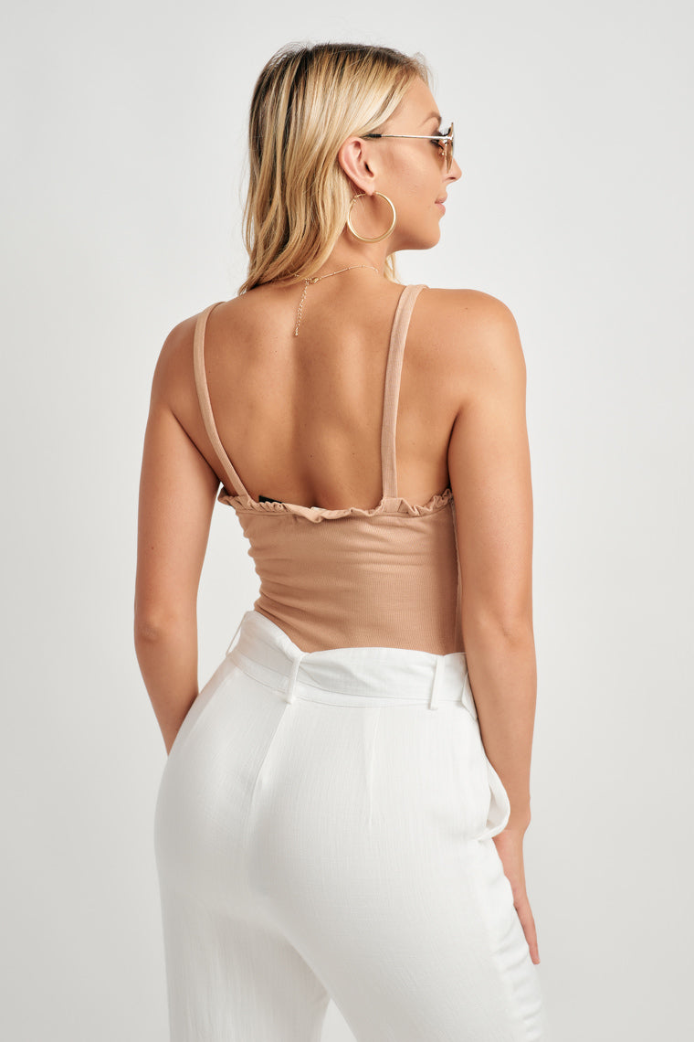 Lightweight, tan ribbed bodysuit offers skinny straps on a ruffled neckline. The button-down bodice, figure fitted silhouette, finishing with a button snap.