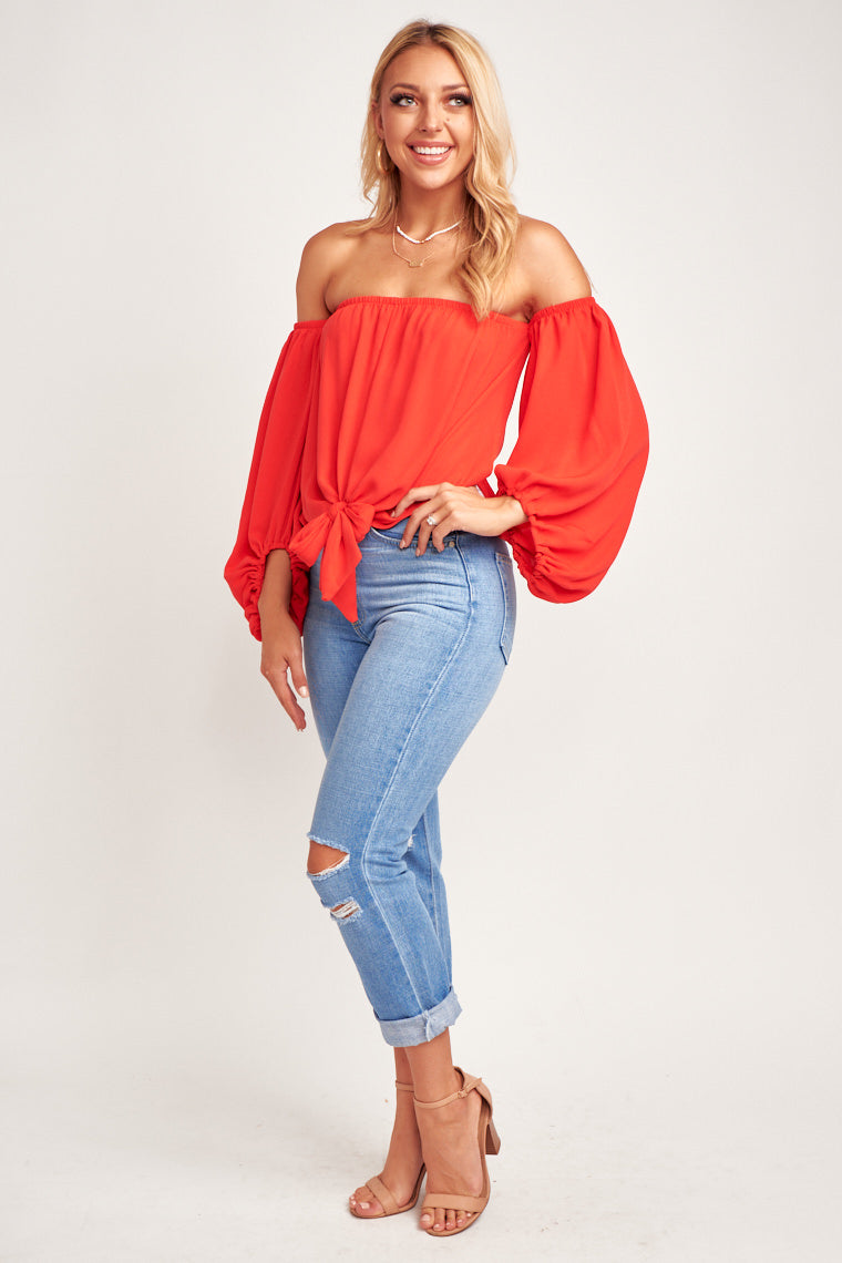 This red hot top has oversized and elastic cuffed puff sleeves that attach to a straight neckline and relaxed oversized bodice with a tie-front hem at the bottom.