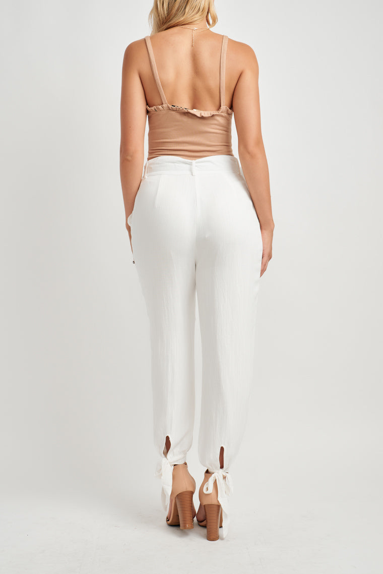 This lightweight, white linen pants have a high-rise, belted waistline with an invisible zipper fly, side cut pockets and a billow pant leg with a tying ankle cuff.