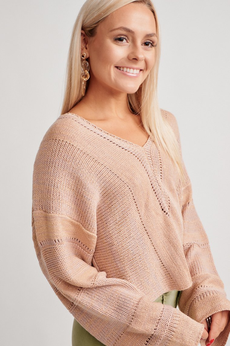 This stripe knit sweater has long sleeves that attach to a v-neckline and lead into a relaxed fit bodice silhouette. Pair with a denim skirt and thigh-high booties.