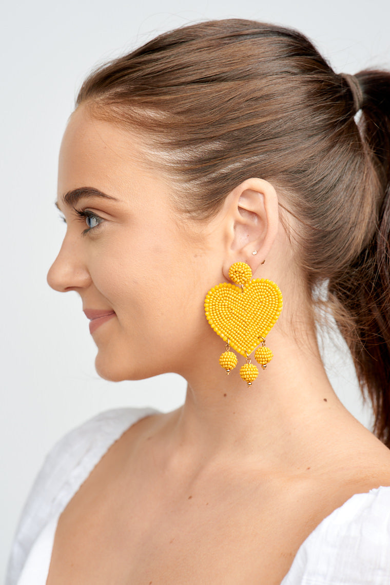 These earrings have a post that attaches to a circular beaded piece that leads to a large beaded heart with a lighter tone bead trim and ends with three beaded spheres that dangle off of it.
