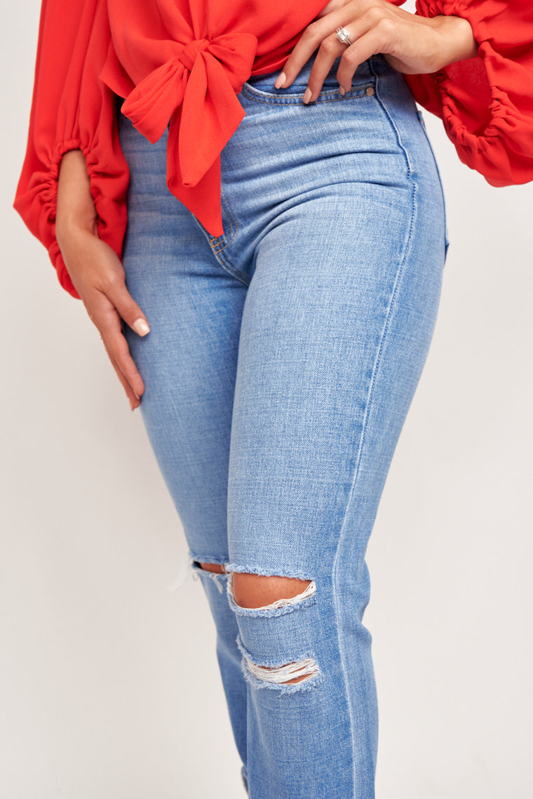 These light wash denim jeans are high waisted with an oversized and loose fit. They have distressed details at knees to add a worn finish. Perfect to style with any top!
