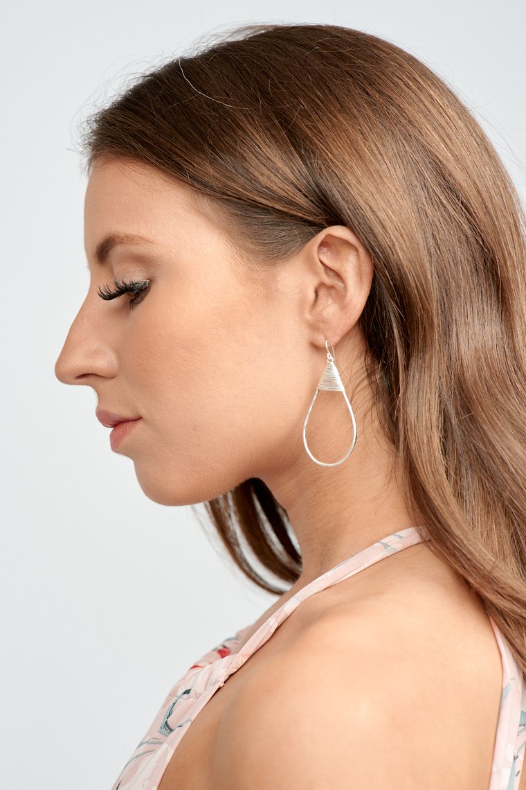 These earrings have a curved post that leads to a hammer-textured wire that forms a teardrop shape and has fine silvery threads that detail the top of the earrings.