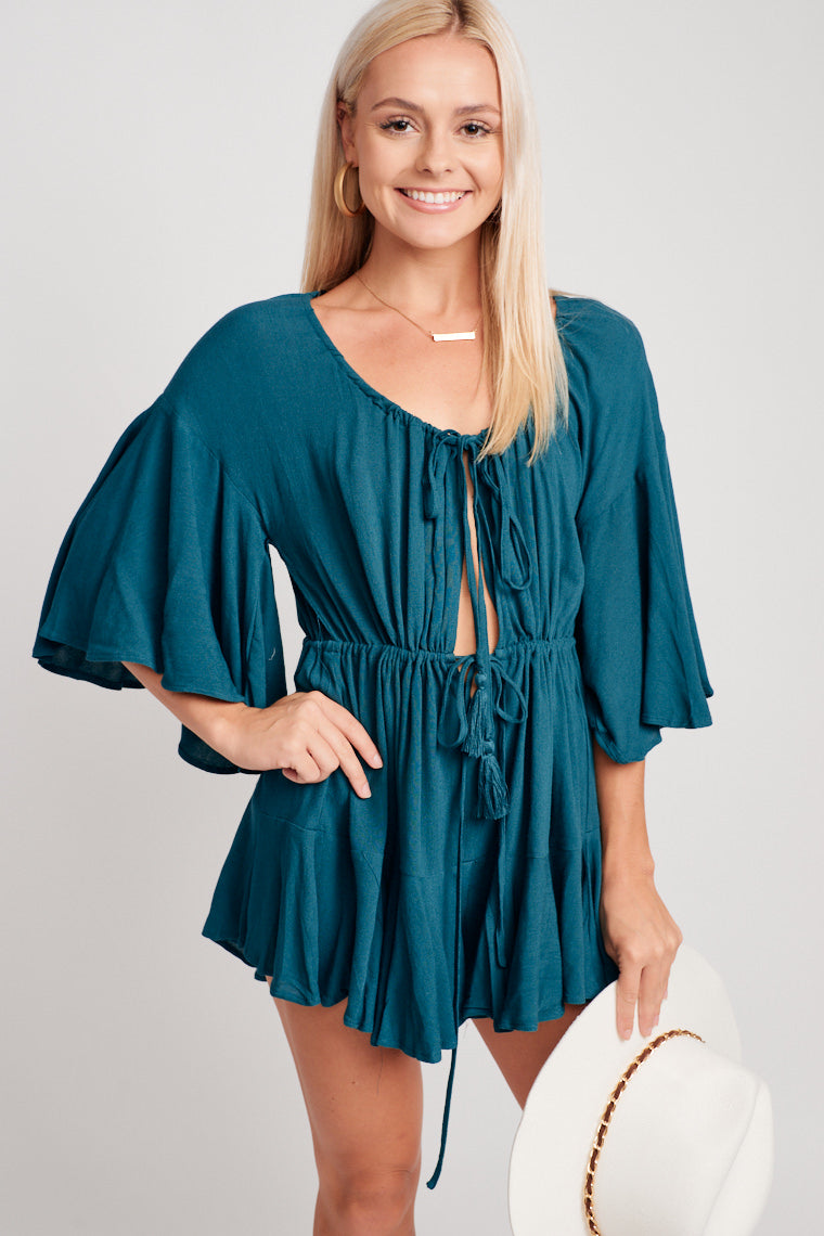 Mid-length flutter sleeves attach to a v-neckline, relaxed bodice has an opening and leads to a drawstring waist and goes into large flowy and flirty shorts.