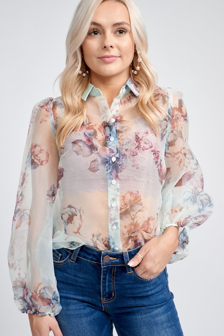 Multicolor floral prints cover the fabric of this sheer button-down blouse. Long banded puff sleeves attach to a collared neckline on a relaxed button-down bodice.