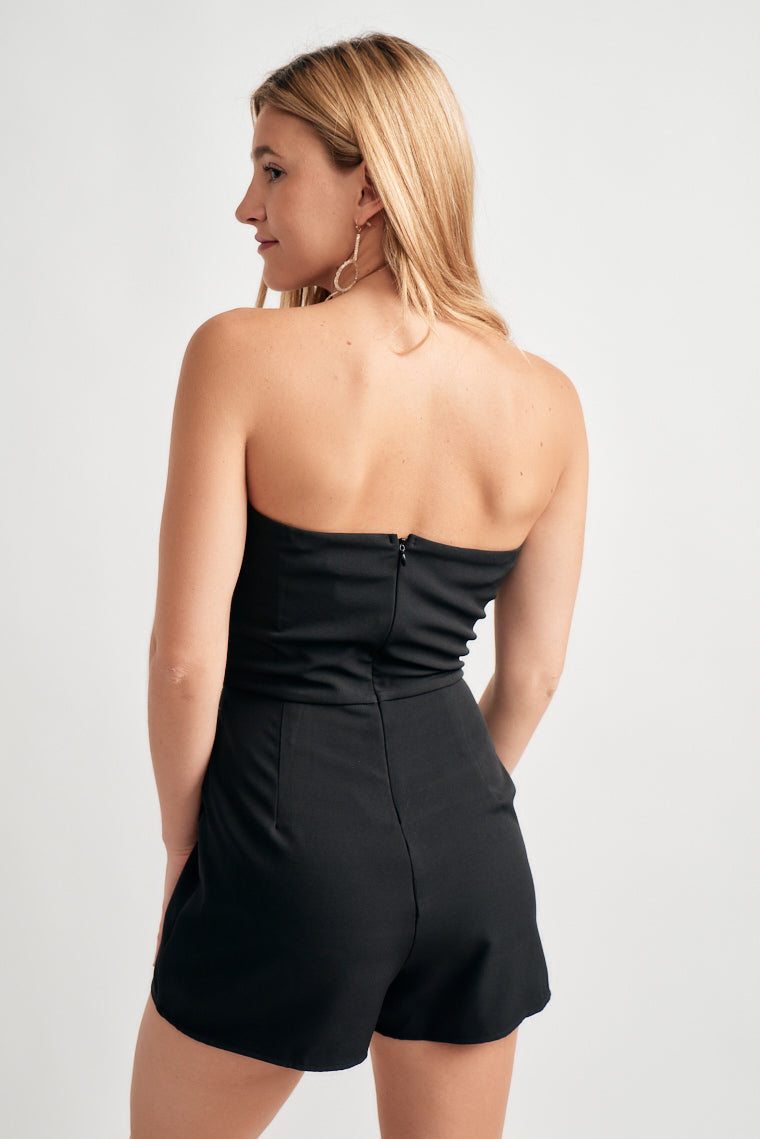 Black strapless romper, side seam bodice with a no-slip grip along the neckline, and a fitted waistline carrying into relaxed shorts with side seam pockets.
