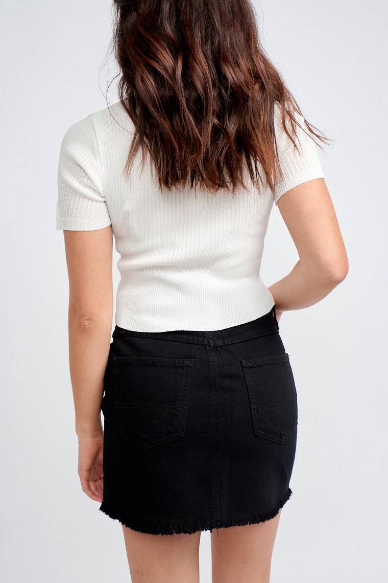 This classic black denim skirt has a fitted button and zipper waistband with a traditional 5-pocket structure and leads to an a-line skirt with a raw frayed hem.