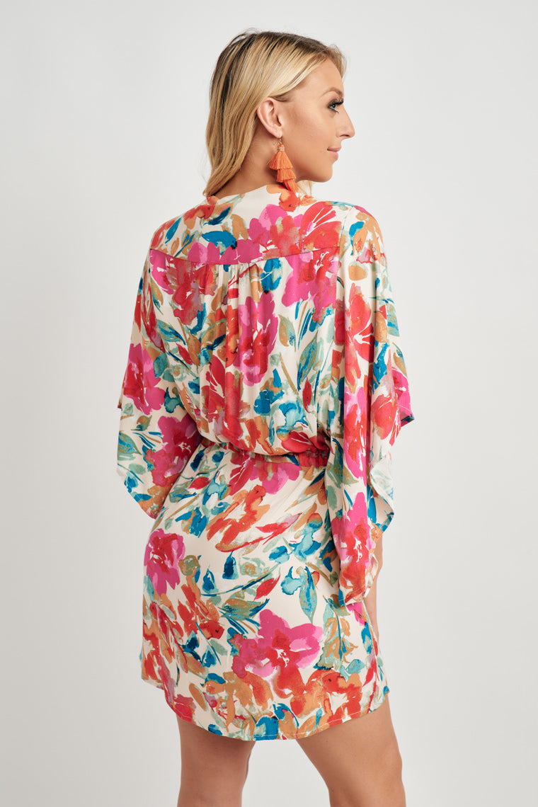 This beautiful floral print decorates this long, kimono sleeve dress with a v-neckline accented by a button-down bodice atop a drawstring waistline and a mini, high-low hem