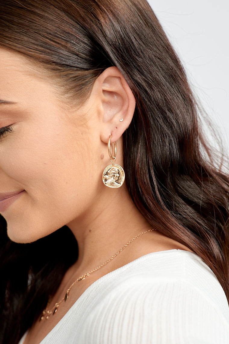 The Victoria Gold Coin Hoops add the perfect touch to any casual outfit as it drops down your ears.