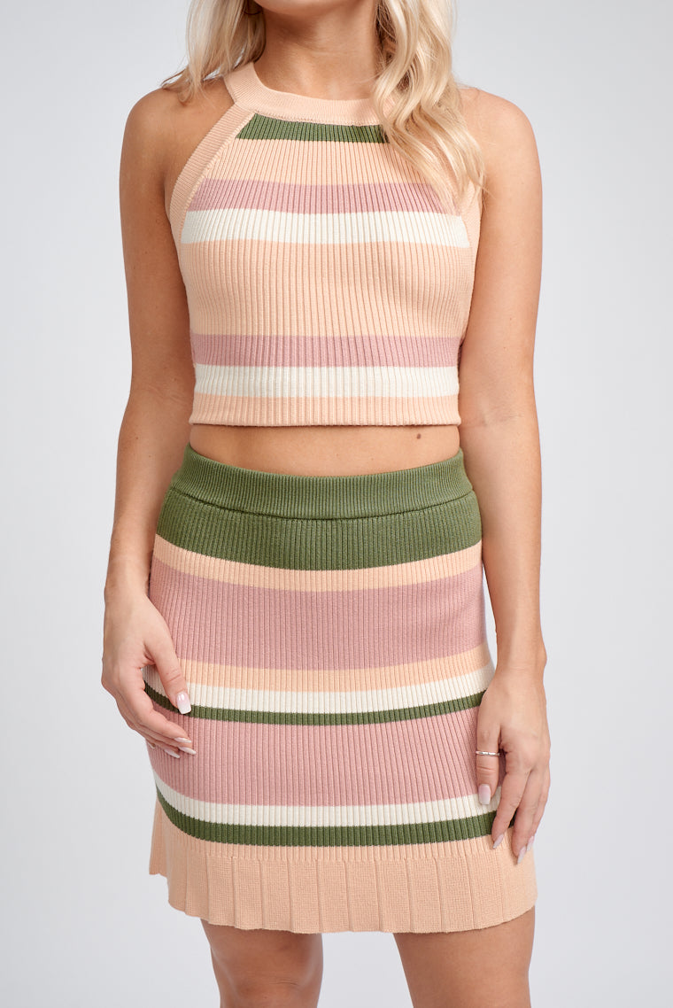 Shades of pink and olive stripes run across this skirt. It has an elastic waistband that leads to a fitted and ribbed mini pencil skirt with a pleated hem across the bottom.