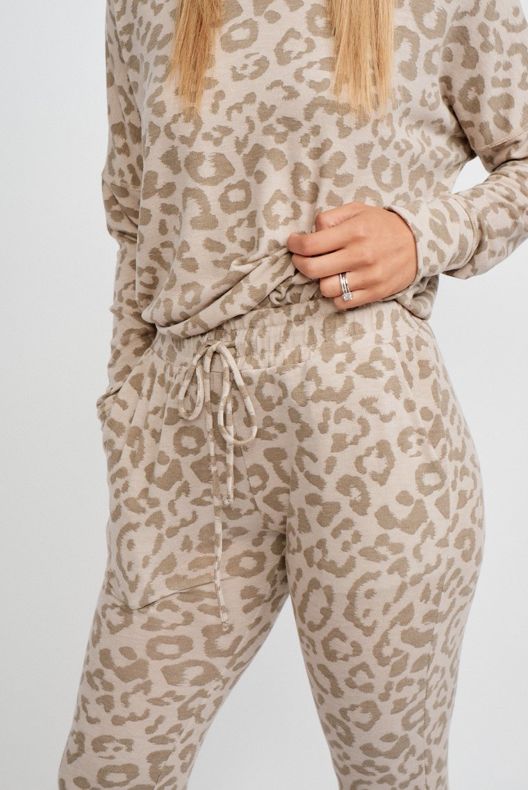 Leopard spots speckle the fabric of this super cozy sweatpants. It has an elastic drawstring waistband and leads down to side pockets and fitted pant legs with elastic ankle cuffs.