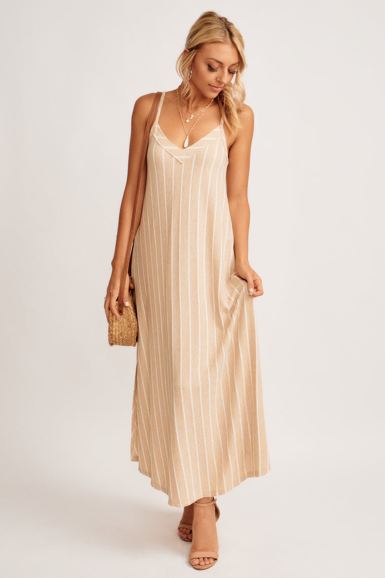 This dress is so easy to wear and is great for numerous occasions. This taupe dress is striped with ivory on soft woven fabric, has a v-neckline and a flowy silhouette.