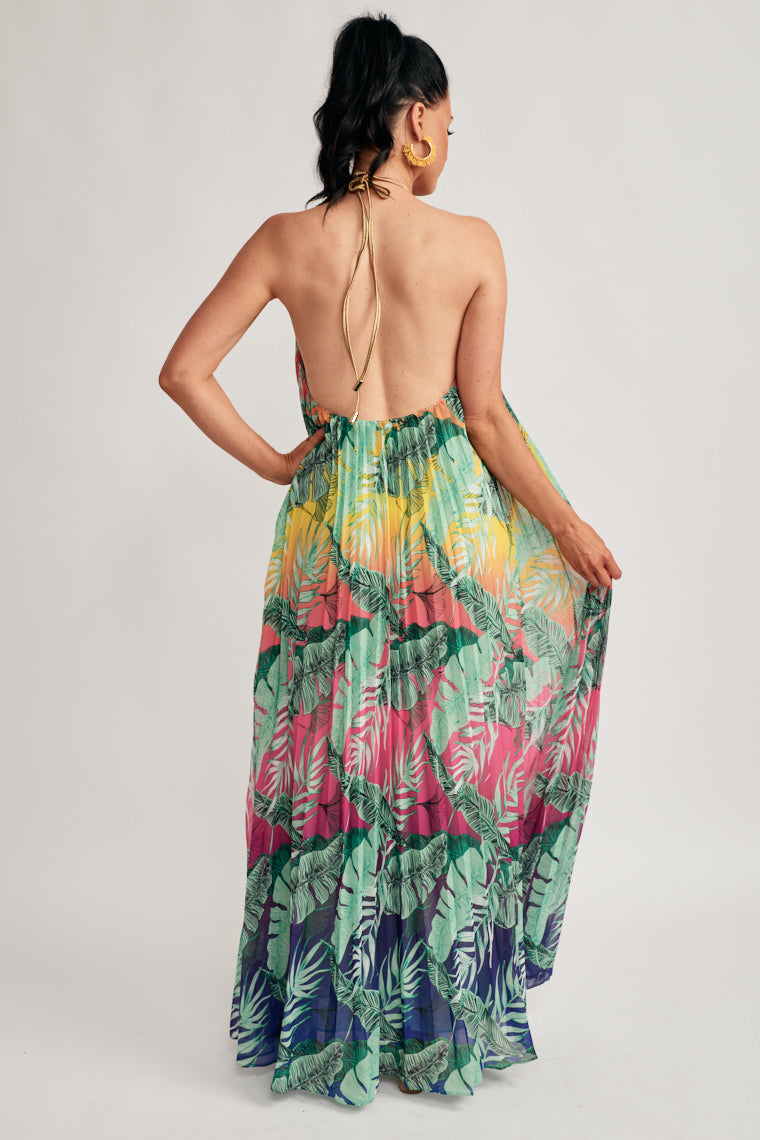 This stunning maxi dress has a rope halter neckline that falls into a beautifully accordion pleat silhouette with a tropical leaf print on an ombré background.