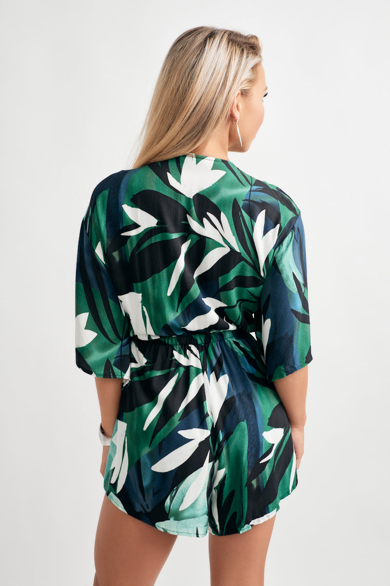 tropic print decorates this short sleeve romper that offers a tie front neckline leaving a midriff cut out above the cinched waistline and relaxed shorts.